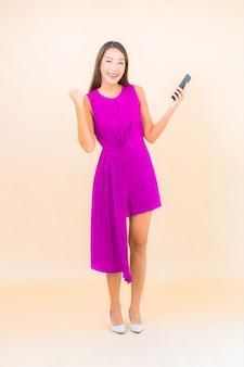 Gebruik slimme mobiele telefoon van de portret mooie jonge aziatische vrouw op kleurenachtergrond