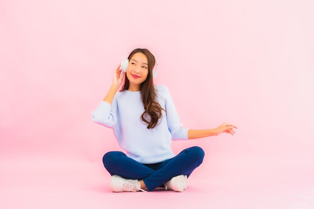 Gebruik van de portret mooie jonge aziatische vrouw slimme mobiele telefoon met hoofdtelefoon om muziek op roze muur te luisteren