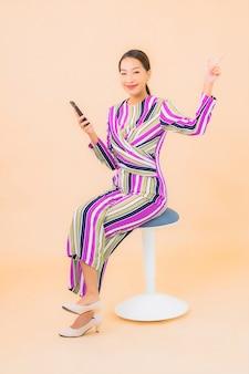 Gebruik van de portret mooie jonge aziatische vrouw slimme mobiele telefoon op kleur