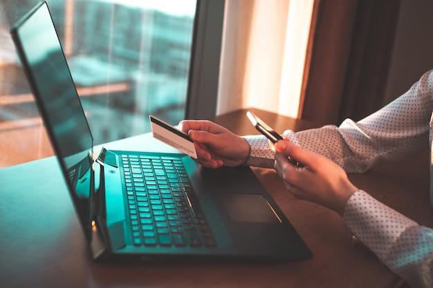 Gebruik van een laptop, creditcard en mobiele telefoon om goederen te kopen en te betalen.
