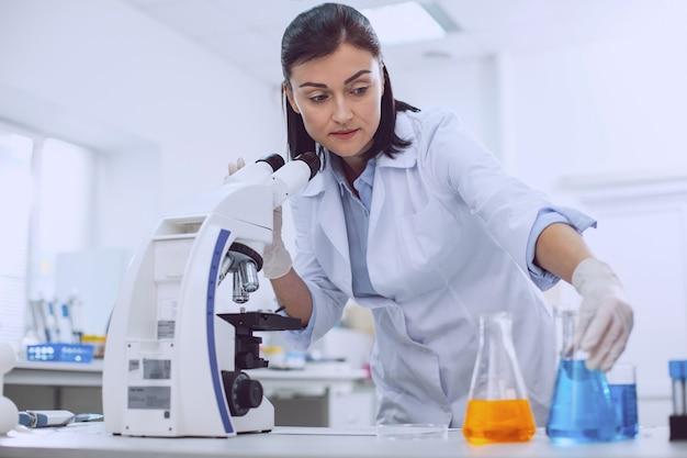 Gebruikelijk werk. ernstige bekwame wetenschapper die met een microscoop werkt en de buizen aanraakt