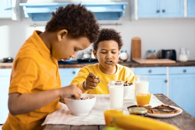Gebruikelijke ochtend. charmante jongens met krullend haar die aan tafel zitten en een gesprek voeren terwijl ze 's ochtends ontbijtgranen eten