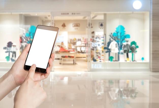 Gebruikend smartphone in een markt of een warenhuis, close-up