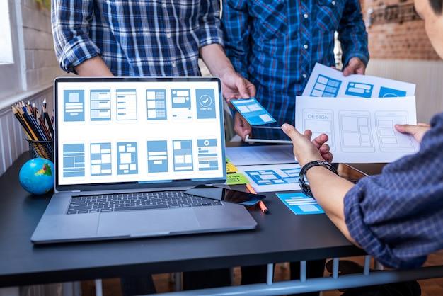 Gebruikerservaring teamwork mobiele ux / ui-ontwerpers die werken in de werkruimte voor co-working space.