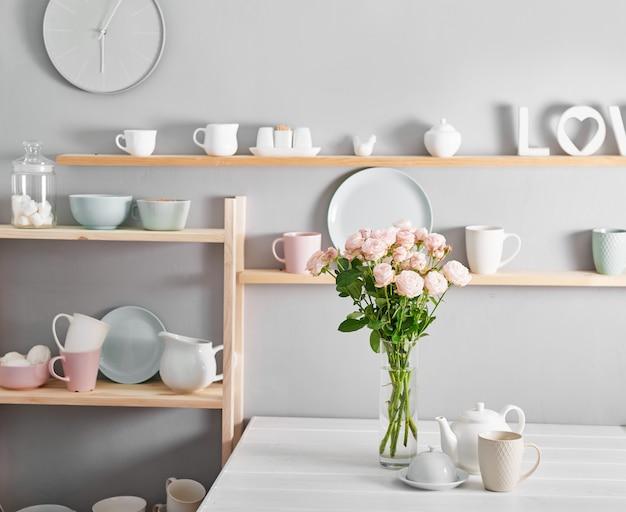 Gebruiksvoorwerpen, boeket rozen en mokken op de plank. gerechten in de kast in de keuken.