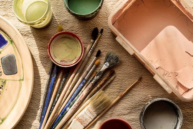 Gebruiksvoorwerpen en verf voor het concept van het aardewerk van keramische vazen