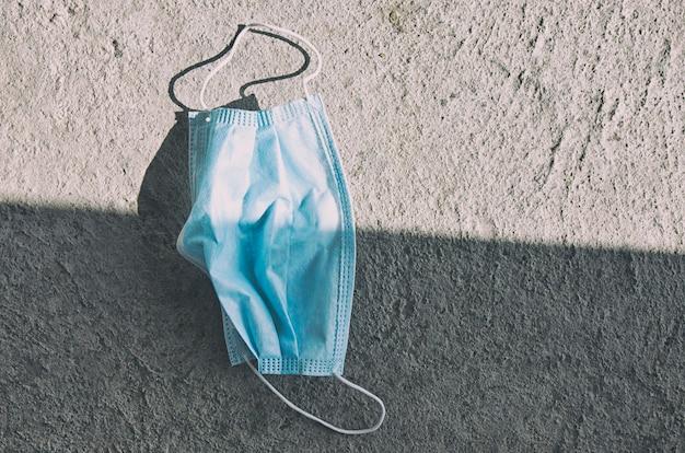 Gebruikt gezichtsmasker liggend op de betonnen vloer in de straat