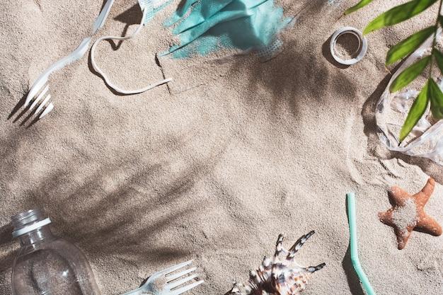 Gebruikt medisch masker en plastic afval weggegooid op zandstrand