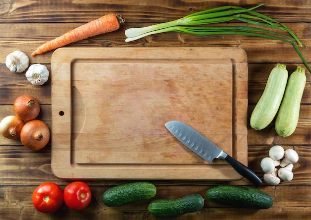 Gebruikt rustiek houten hakbord, mes en rauwe groenten op donkere tafel
