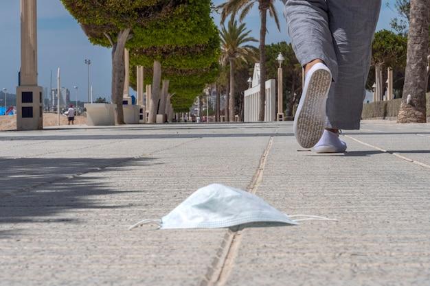 Gebruikt verloren beschermend medisch gezichtsmasker op de grond