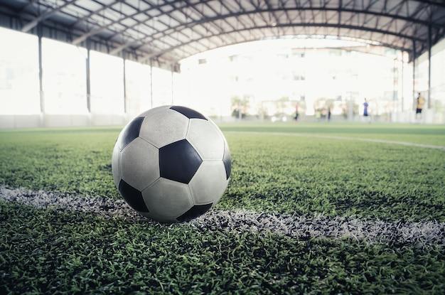 Gebruikt versleten klassiek zwart-wit voetbal op trainingsveld