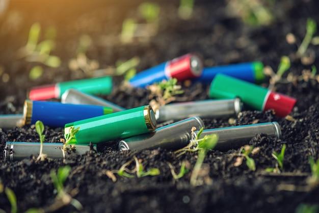 Gebruikte alkalinebatterijen liggen in de grond waar planten groeien.