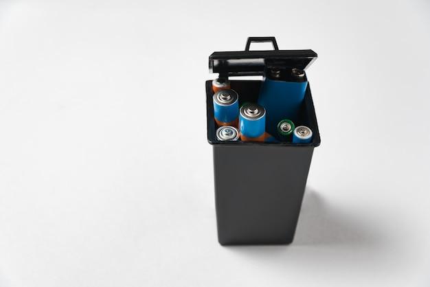 Gebruikte batterijen in zwarte huisvuilcontainer op witte achtergrond. recycling batterijen concept