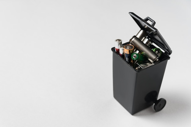 Gebruikte batterijen van het vingertype in de prullenbak. ecologie recycling concept. correcte verwijdering van batterijen en accu's.