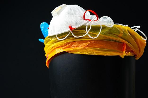 Gebruikte besmettelijke maskers en medische handschoen in de prullenbak