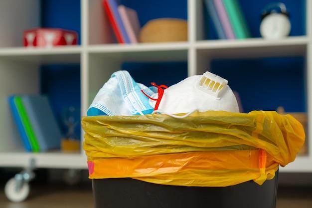 Gebruikte besmettelijke maskers in de prullenbak van dichtbij