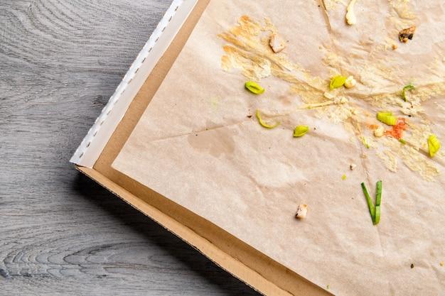 Gebruikte geopende pizzadoos met vlekken en kruimels aan de binnenkant op tafeloppervlak. thuisbezorging en thuis blijven concept.