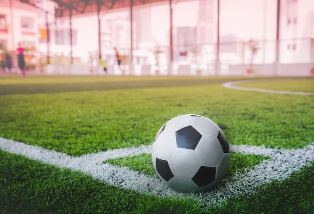 Gebruikte klassieke zwart-witte voetbalbal op de hoek van het voetbalveld