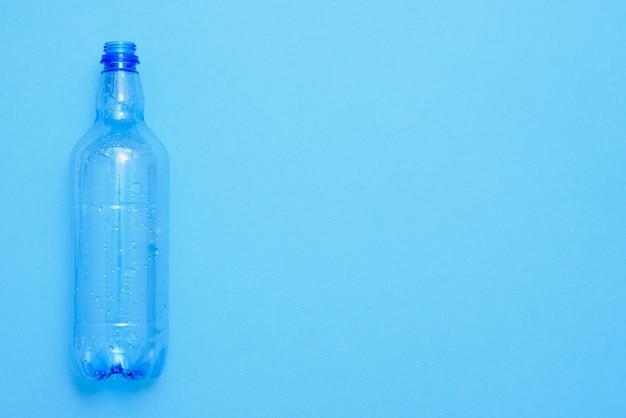 Gebruikte plastic flessen op de blauwe achtergrond