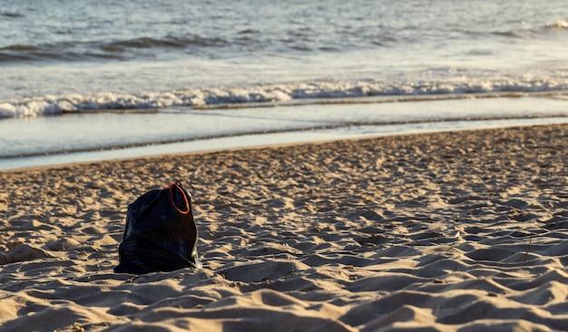 Gebruikte plastic zakafval en afval op strandzand voor milieukwestieconcept.