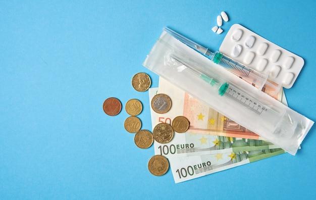 Gebruikte tablet blaren en geld op blauwe achtergrond. duur medicijnconcert