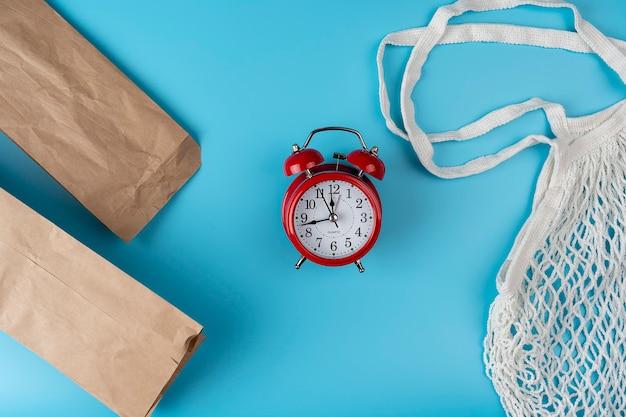 Gebruikte tassen gemaakt van recycle papier met katoenen tas met rode wekker concept zero waste