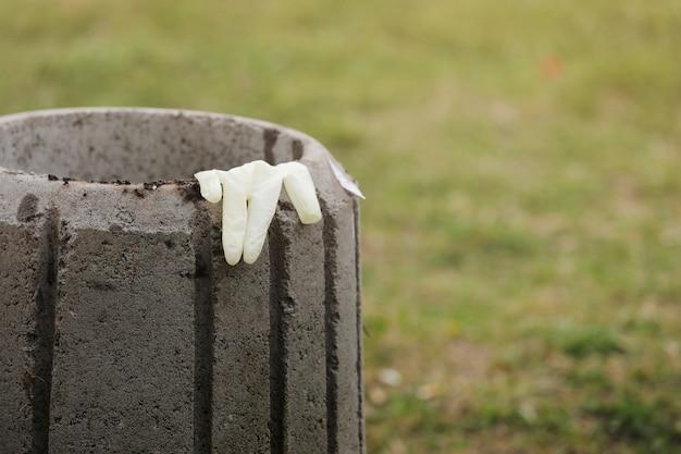 Gebruikte wegwerphandschoen op een huisvuilcontainer dicht omhoog. verwijdering van het concept van persoonlijke beschermingsmiddelen. selectieve aandacht