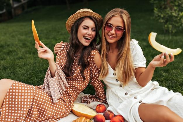 Gebruinde brunette krullende vrouw in stijlvolle beige polka dot jurk en aantrekkelijke blonde dame in witte outfit glimlach, picknicken en genieten van meloen