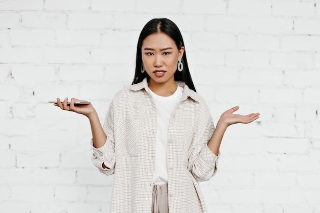 Gebruinde brunette vrouw in beige jas kijkt met misverstand in de camera Gratis Foto