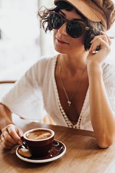 Gebruinde brunette vrouw in bruine pet en zonnebril houdt bruin porseleinen kopje koffie en rusten in café