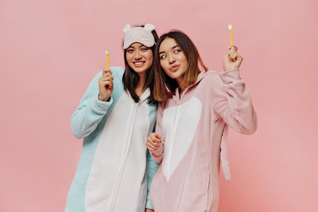 Gebruinde charmante aziatische meisjes in schattige zachte pyjama's glimlachen en houden gele tandenborstels op een geïsoleerde roze muur