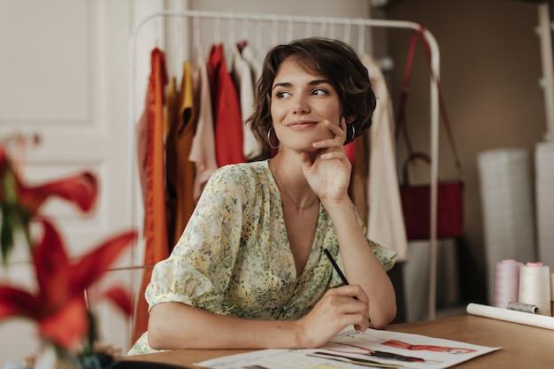 Gebruinde, coole brunette kortharige vrouw in gele bloemenjurk glimlacht oprecht, creëert nieuwe modecollecties en zit aan het bureau