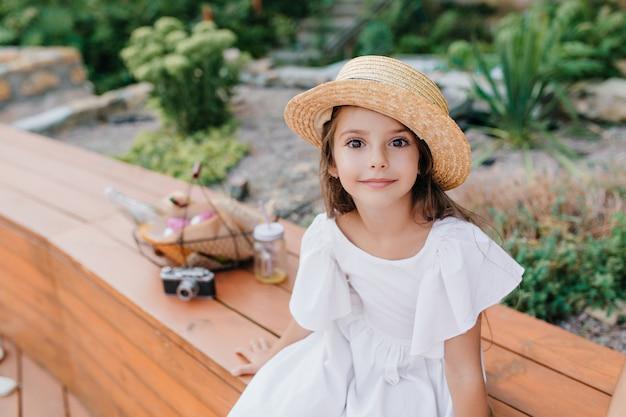 Gebruinde dame in vintage strooien hoed zittend op een houten bankje met mandje voor picknick en camera. outdoor portret van donkerogige meisje draagt witte jurk poseren