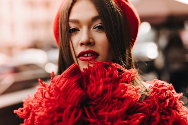 Gebruinde donkerharige vrouw in rode wollen jas en baret camera kijken tegen de achtergrond van de stad straat.