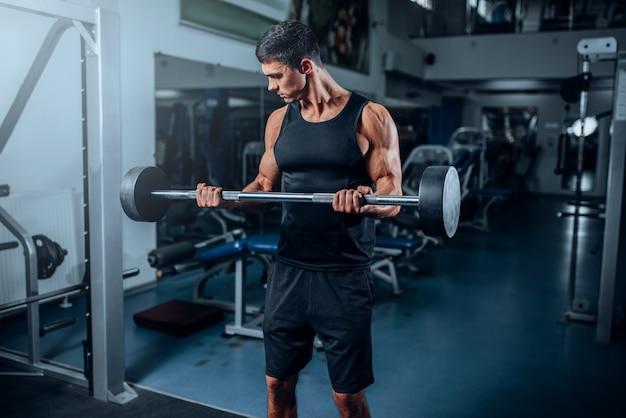 Gebruinde gespierde man training met barbell in sportschool. actieve training in sportclub