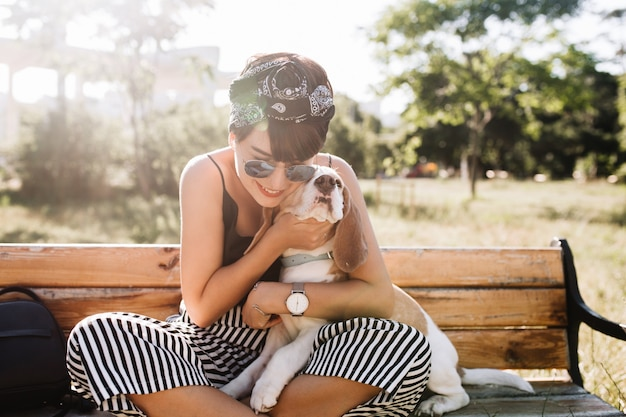 Gebruinde glimlachende dame in elegant polshorloge beagle hond omarmen tijdens rust in park in de ochtend