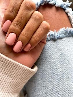 Gebruinde hand van een vrouw met een zachte beige-roze manicure, bedekt met gellak