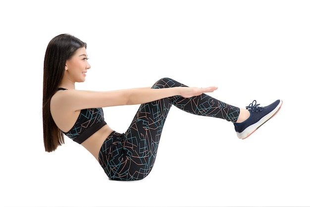 Gebruinde huid. asian fitness girl in sexy cute sport bra zwarte spandex broek oefening opwarmen. fitness training. door geïsoleerde witte achtergrond.
