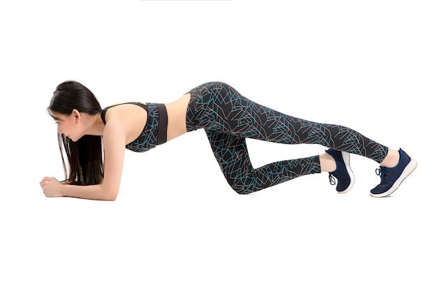 Gebruinde huid. asian fitness girl in sexy cute sport bra zwarte spandex broek oefening opwarmen. oefeningen voor de heupen en dijen. door geïsoleerde witte achtergrond.