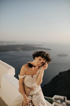 Gebruinde jonge vrouw in beige jurk met strozakje houdt telefoon vast en kijkt naar buiten looks