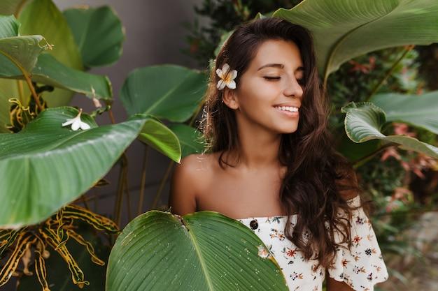 Gebruinde langharige vrouw in witte top met bloemenprint, genietend van de zomerdag op vakantie in een warm land