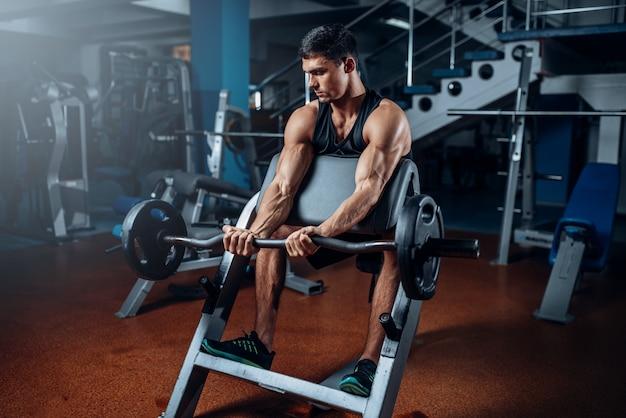 Gebruinde man oefenen met barbell in sportschool. actieve training in sportclub