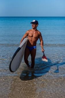 Gebruinde man op het strand met een surfplank en riem in zijn handen gaat het water in.