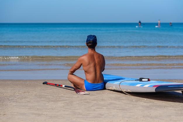 Gebruinde man zit op het strand in de buurt van zijn surfplank en kijkt naar de zee.