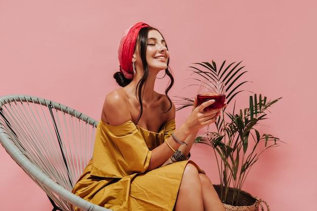 Gebruinde slanke dame met golvend haar in felgele outfit en accessoires glimlachend met gesloten ogen en poserend met een glas rode wijn