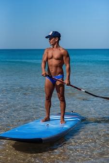 Gebruinde sportieve man in een pet staat op zijn surfplank op het water, houdt een riem vast en kijkt in zee.