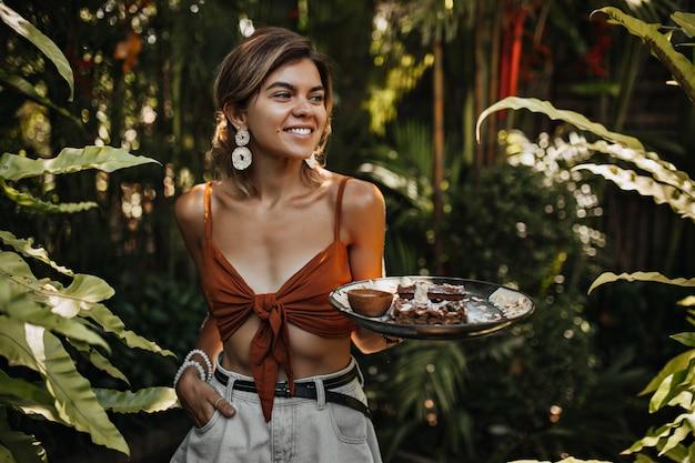 Gebruinde vrouw in korte broek en bruine beha glimlacht en houdt bord met wafel en noten