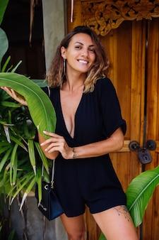 Gebruinde vrouw met kort krullend haar in zwarte sexy overall bij deur van tropische villa op vakantie bij zonsonderganglicht