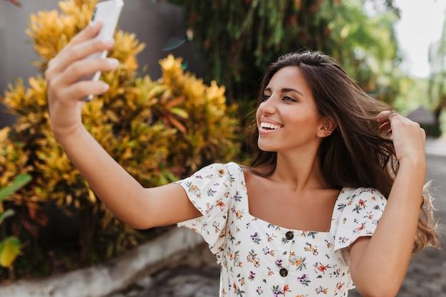 Gebruinde vrouw raakt haar lange donkere haar aan en neemt een selfie tegen een muur van bomen