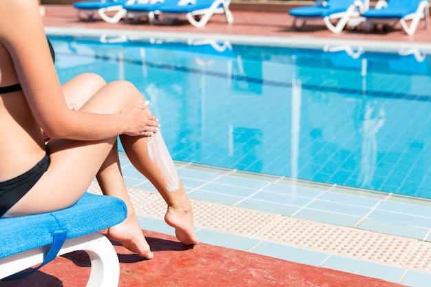 Gebruinde vrouw zit bij het zwembad en brengt sunblock aan om haar huid te beschermen tegen zonnebrand. zonbeschermingsfactor in vakantie, concept.